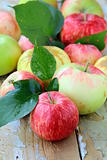 Red,green and yellow apples with leaves on wooden table