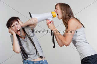 angry woman yelling into a megaphone to another scared girl - isolated on gray