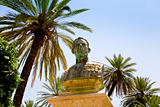 old bronze bust under palm trees