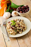 Risotto with black olives on wooden table