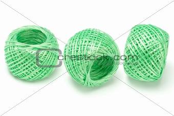 Three balls of green nylon string