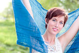 Outdoor Portrait of Pretty Blue Eyed Young Red Haired Adult Female with Blue Scarf.
