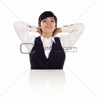 Attractive Smiling Mixed Race Young Adult Female Sitting At White Table with Hands Behind Her Head Isolated on a White Background.