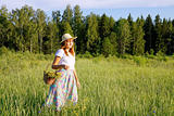 Girl with a basket is on the meadow