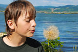 Boy blowing on flower