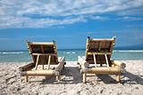 Wooden deckchairs on empty beach
