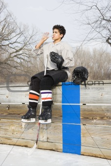 Hockey boy drinking water.