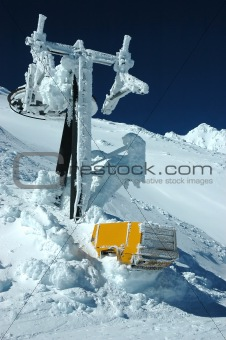 Ski lift must after snow fall in mountains.