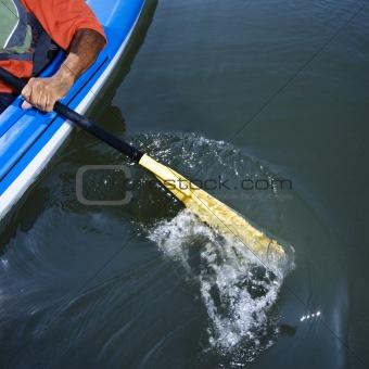 Man paddling kayak.