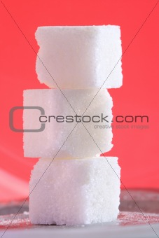 Three sugar cubes on the pink background