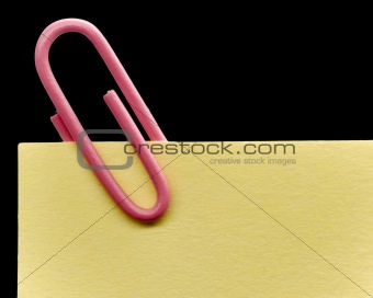 Pink paperclip on a yellow note with white background