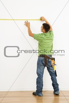 Man measuring wall.