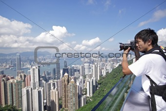 Tourist taking photo of Hong Kong skyline by his digital camera