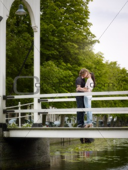 Boyfriend and girlfriend kissing on bridge