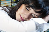 Beautiful student girl with smile on her face sleeping on books