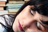 Beautiful young school girl in library sleeping