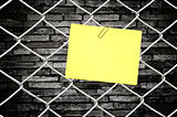 yellow note on chain link fence and old wall