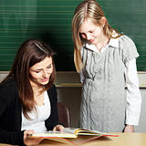 Student and teacher in the classroom look together in a school book - square