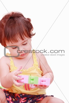 Baby in yellow shirt playing with toys