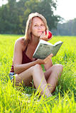 Young woman sitting in grass reading book an apple in her hand