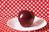 Red juicy apple on a white plate