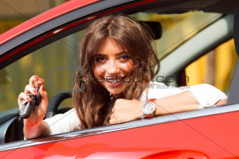 Beautiful young  woman in the new car with keys