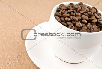 Close coffee cup filled with coffee beans