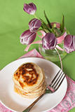 Delicious pancakes for breakfast and a vase with a bouquet of tulips