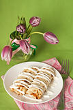 Pancakes with sour cream for breakfast and a vase of purple tulips