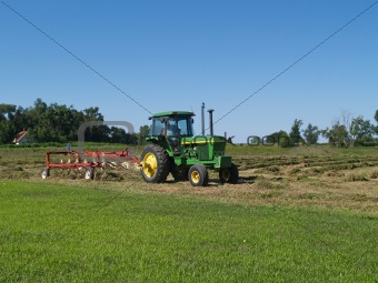 Tractor With Hay Rake Working in a Field
