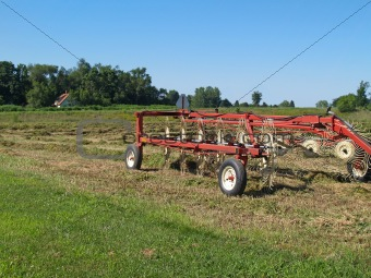 Hay Rake Sitting in a Field of Just Raked Hay