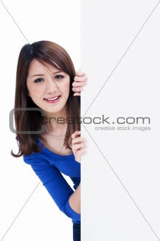 Cute young woman holding blank signboard
