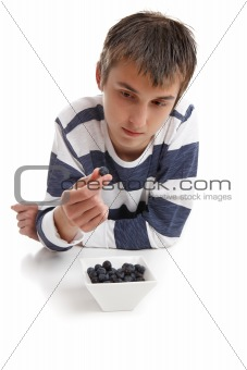 Boy inspecting blueberry