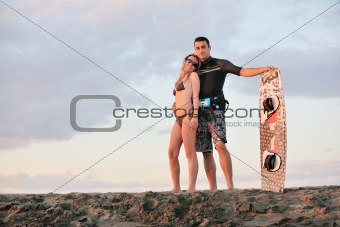 surf couple posing at beach on sunset