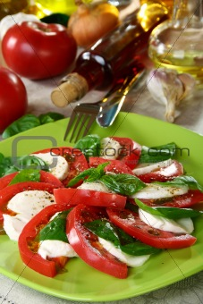 Salad caprese with fresh tomatoes, cheese and basil.