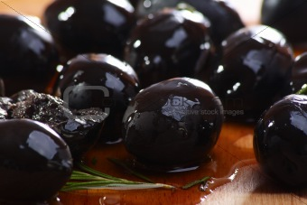 Black olives on a wooden table.
