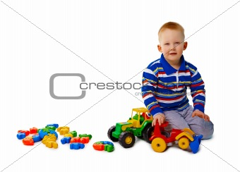 Boy sits on white background with toys