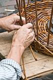 Man's hands making a wicker basket