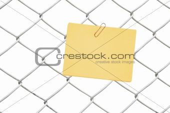 yellow note on chain link fence