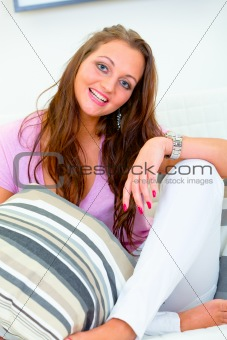 Smiling beautiful young woman relaxing on white divan