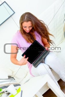 Attractive woman sitting on sofa and pointing in laptops blank screen