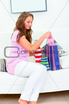 Attractive woman sitting on sofa with shopping bags and checking purchasing