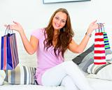 Cheerful lovely woman sitting on sofa and holding shopping bags in hands