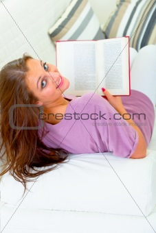 Smiling attractive woman sitting on white sofa with book