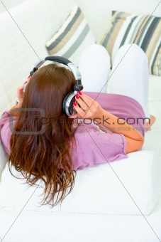 Woman sitting on sofa and listening music in headphones