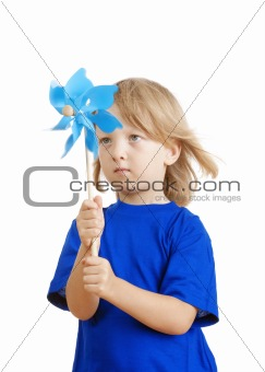 boy with long blond hair in blue top playing with a pinwheel - isolated on white