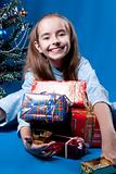 Girl and christmas presents near christmass tree