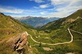 Unpaved road in the valley in Alps, italy.