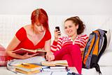 Responsible girl studying while her girlfriend reading sms