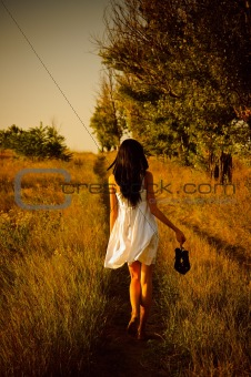 Barefoot girl in white dress with shoes in hand is on the field.